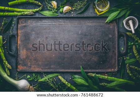 Food background with free space for text. Herbs, olive oil, spices around cast iron frying board. Top view.