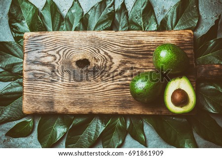 Food background with fresh avocado, avocado tree leaves and wooden cutting board. Harvest concept, Guacamole ingredients. Healthy fat, omega 3. Half of avocado. Top view. Copy space