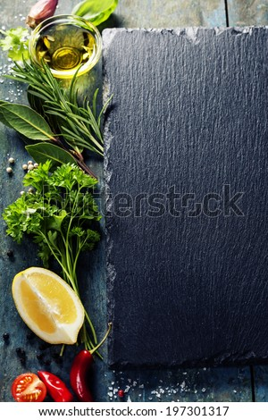 Food background, with herbs, spices, olive oil, salt, lemons and vegetables. Slate and wood background.