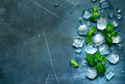 Food background with ice cubes and mint leaves on a blue slate, stone or concrete table.. Top view with copy space.