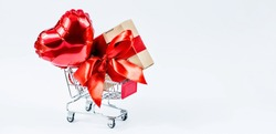 Food basket, gift box and heart-shaped balloon. Online stores. Winter Holiday Sales, Seasonal Sales, Black Friday, February 14 Valentine's Day. Discounts and on-site purchases.