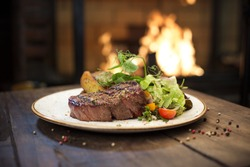 Food - Beef dinner - Delicious grilled stake and potatoes served on a wooden table, fireplace on background. Big steak meat dish on a main course plate