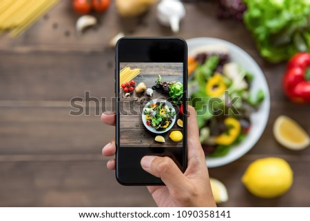 Food blogger using smartphone taking photo of beautiful salad, raw spaghetti and ingredients on wood table to share on social media