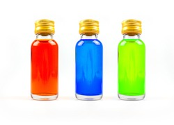 Food coloring in glass bottles on white background isolate, yellow, blue, green, three bottles of food coloring