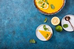 Food concept Homemade organic Lemon, lime tarts or cake  pie on blue stone board