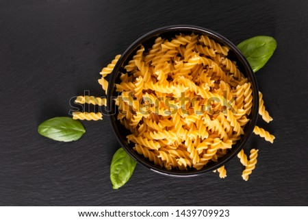 Food concept raw organic Italian Fusili pasta in black bowl on black slate board with copy space Foto d'archivio ©