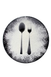 food concept - top view of black plate with spoon and fork imprint on flour or powdered sugar