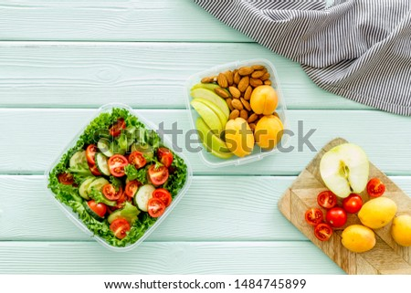 food container with salad on mint green wooden background top view