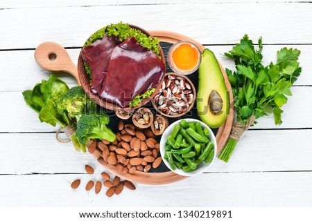 Food containing natural iron. Fe: Liver, avocado, broccoli, spinach, parsley, beans, nuts, on a white wooden background. Top view.
