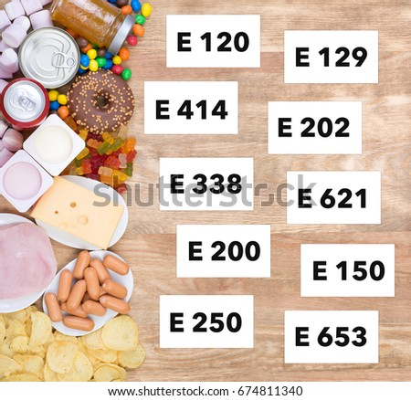 Food containing unhealthy additives on wooden background