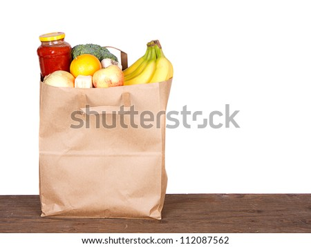 Food contents of a brown paper shopping bag on white