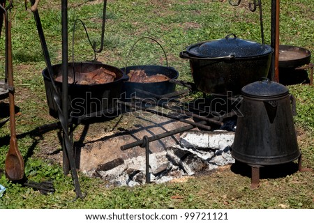 Food cooked over an open fire in cast iron pots and pans
