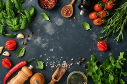 Food cooking background. Fresh rosemary, cilantro, basil, cherry tomatoes, peppers and olive oil, spices herbs and vegetables at black slate table. Food ingredients top view.