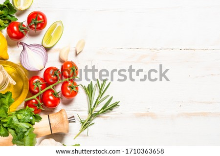 Food cooking background on white wooden table. Fresh vegetables, spices, herbs and oil. Ingredients for cooking with space for your text.