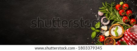 Food cooking background. Spices herbs and vegetables at black slate table. Food ingredients top view long format. Stockfoto ©