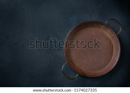 Food cooking concept. Empty cast iron frying roasting pan on a dark background. Flat lay, top view, copy space
