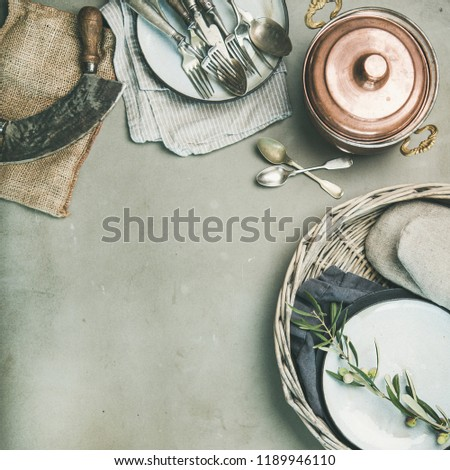 Food cooking minimalistic background. Flat-lay of various kitchen utensils, copper saucepan, vintage cutlery over grey concrete countertop background, top view, copy space, square crop