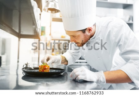 food cooking, profession and people concept - happy male chef cook serving and garnishing stewed vegetables on plate at restaurant kitchen