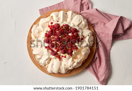 food, culinary, baking and cooking concept - close up of pavlova meringue cake decorated with red berries on wooden serving board and kitchen towel Stock photo ©