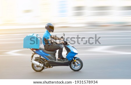 Food delivery boy on motorcycle moving fast to deliver food to customers, home and office delivery on motorbike, pizza online order. Express delivery service from cafes and restaurant, internet orders