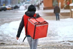 Food delivery boy walking on city street in wintertime, hurry up to deliver online food orders to customers. Online commerce - food delivering from favourite restaurants. Delivery man in snowy day