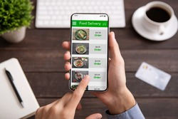 Food delivery. Businessman choosing meal for lunch in takeaway restaurant service on mobile application on smartphone