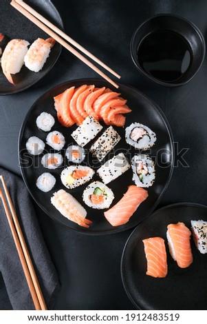 Food delivery coronavirus. Sushi maki rolls  with salmon, avocado, cream cheese. Sushi menu. Japanese food. Black background. Top view.