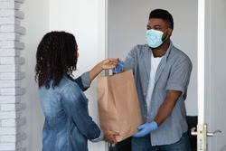 Food delivery during coronavirus. Black courier guy wearing medical mask delivering grocery order to young woman's home