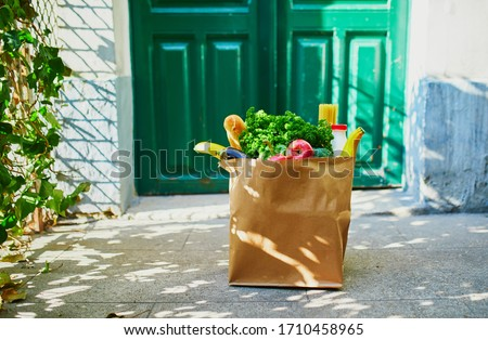 Food delivery during coronavirus outbreak. Paper bag with grocery order in front of the door in Paris, France during Covid-19 epidemic. Safe online shopping, food donation or takeout meal concept