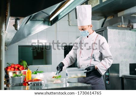 Food delivery in the restaurant. The chef prepares food in the restaurant and packs it in disposable dishes