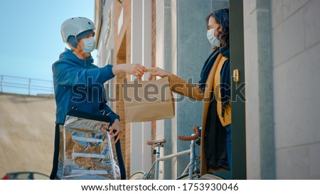 Food Delivery Man Wearing Protective Medical Face Mask and Thermal Backpack on a Bike Delivers Order to a Masked Female Customer. Courier Delivers Takeaway Lunch. Quarantine, Social Distancing