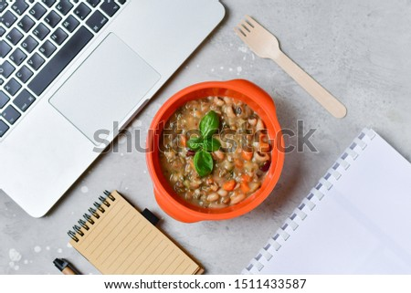 Food delivery. Round lunch box with a diet lunch or dinner on grey office table. Stewed beans with vegetables, takeaway lunch at the office. Top view. takeout healthy lunch. selective focus