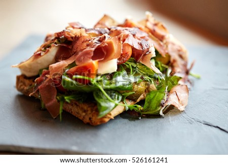 food, dinner, haute cuisine and eating concept - prosciutto ham salad on stone plate at restaurant #526161241