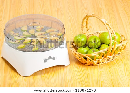 Food dryer and green apples on table