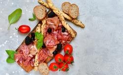 food flat lay italian  antipasti prosciutto, salami, bresaola olives tomatoes and grissini bread sticks. aperitif happy hour