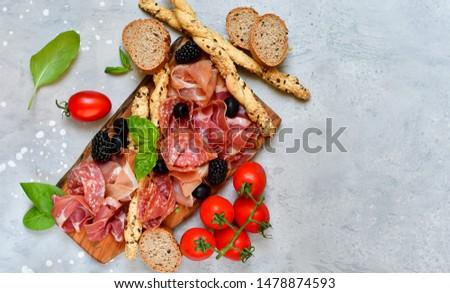food flat lay italian  antipasti prosciutto, salami, bresaola olives tomatoes and grissini bread sticks. aperitif happy hour Stock photo ©