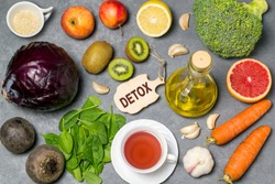 Food for detoxification. Detox food purify body of toxins, have beneficial health effects. Concept of purification. Small cutting board with word detox. Top view
