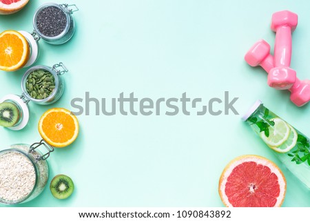 Food for fitness, healthy lifestyle frame flat lay with fresh fat burning fruits orange and grapefruits slices, complex carbohydrates, detox water bottle, pink hand weights, light green background