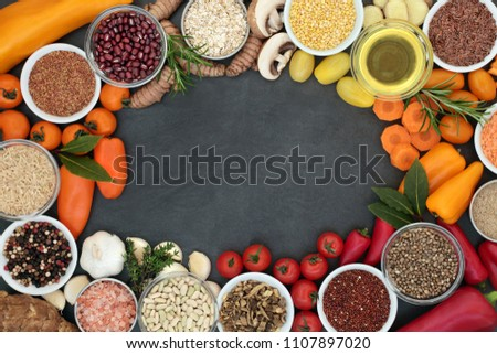 Food for good health and fitness background border with fresh vegetables, legumes, herbs, spice, cereals, oil and seeds on slate background.  High in antioxidants, anthocyanins, minerals and vitamins. #1107897020