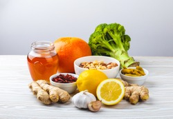 Food for immunity stimulation and viruses protection. Broccoli, citrus fruits, honey, ginger, lemon, garlic, goji, turmeric on white wooden background. Healthy natural food to boost immune system