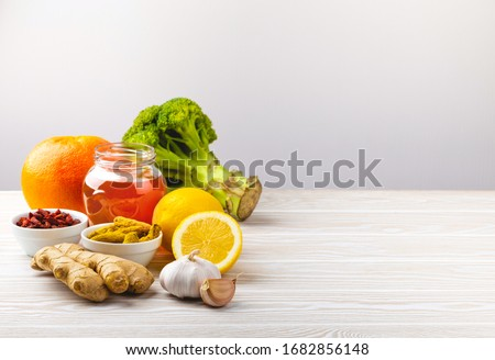 Food for immunity stimulation and viruses protection. Broccoli, citrus fruits, honey, ginger, lemon, garlic, goji, turmeric on white wooden background, copy space. Healthy food to boost immune system