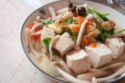 Food for the homeopath, vegan food with organic white tofu, mushrooms and sautéed vegetables on a plate ready to serve. For a healthy meal.