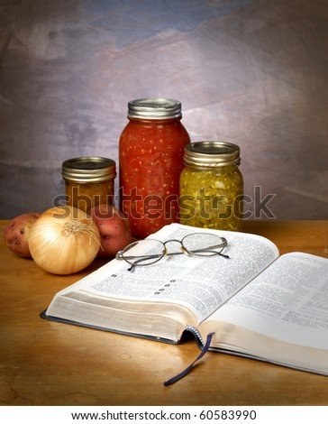 FOOD FOR THOUGHT - canned vegetables and fruit with a bible and pair of glassed on a kitchen counter