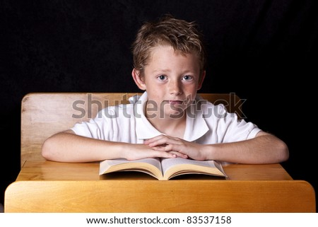 Food for thought.  Happy school child sitting at desk while his head is being filled with nutritious foods.