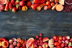 Food frame constructed with red fruits and vegetables, fresh raw organic produce on dark distressed background