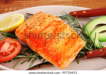 food: grilled salmon on big glass plate on wooden table