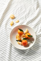 food, healthy eating and fruits concept - close up of mandarins on plate over drapery