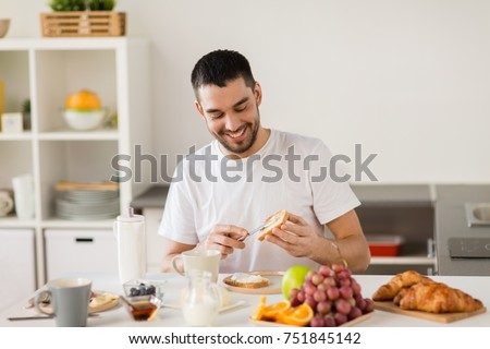 food, healthy eating and people concept - man making toast with cheese spread for breakfast at home kitchen