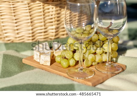 food, holidays, celebration and summer concept - picnic basket with wine glasses, grapes and cheese on wooden board #485665471