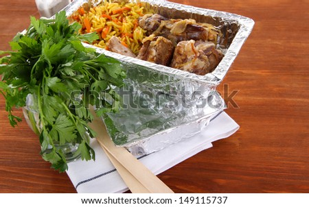 Food in boxes of foil on wooden background